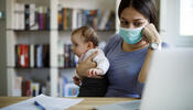Worried parent with mask holding child and using a laptop