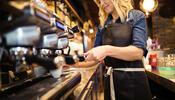 Worker pulling espresso shot in cafe