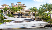 Yacht docked in front of mansion