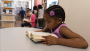 Child reading book at table in school library