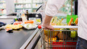 Person going through grocery store checkout with full cart