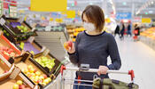 Person wearing mask selecting produce at the grocery store