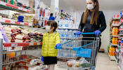 Parent shopping in grocery store with child wearing masks and gloves