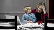 Distressed parent at kitchen table with child and pile of bills