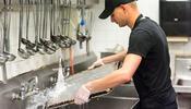 Worker rinsing pan