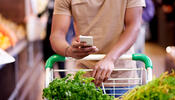 Person looking at their cell phone while grocery shopping
