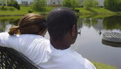 Couple sitting by pond