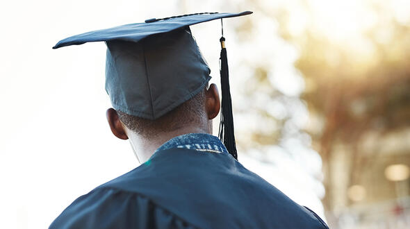 Young person in graduation attire looking away from the camera